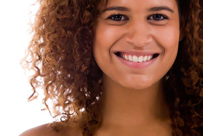 Smiling woman with brown curly hairs